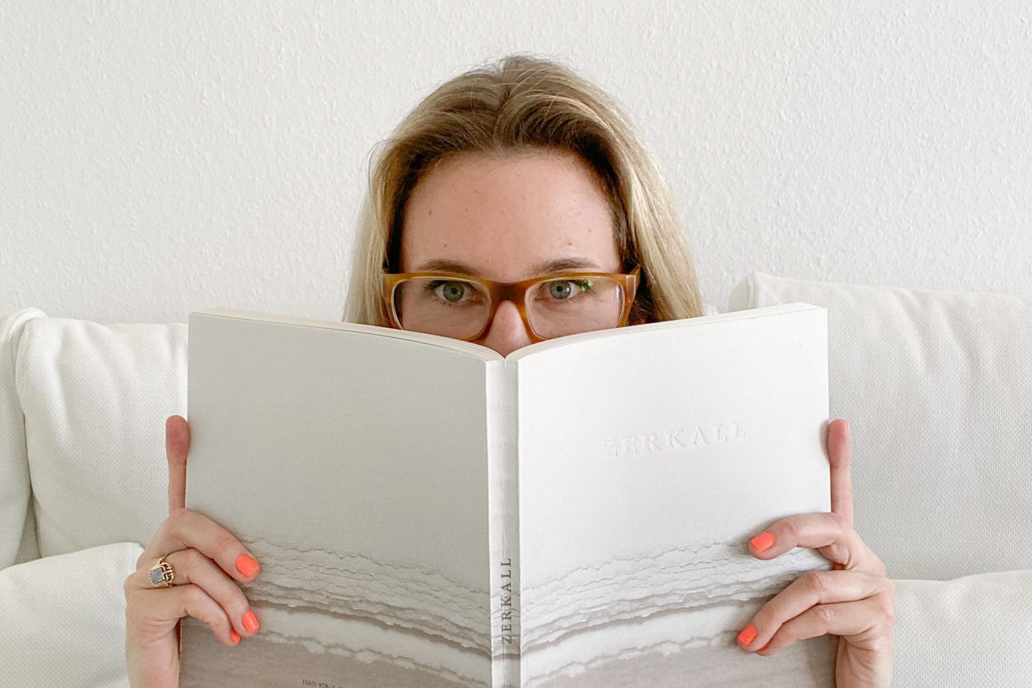 Maxi versteckt sich hinter einem Buch