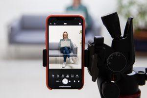 Mit dem Smartphone wird eine Frau fotografiert. Das Display ist im Vordergrund in der Schärfe zu sehen. Im Hintergrund sieht man unscharf die Frau