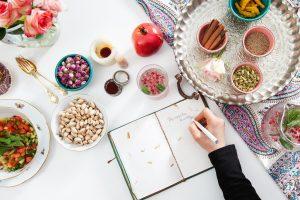 Eine Frau schreibt in ein Rezeptbuch. Der Tisch ist mit persischen Zutaten gedeckt.