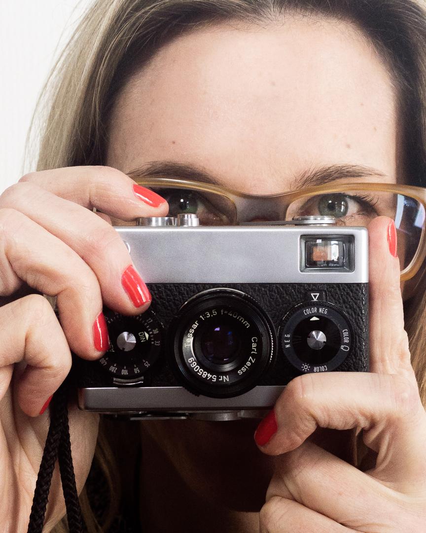 Maxi hält eine kleine analoge Kamera vor ihr Gesicht und lukt über den Sucher.