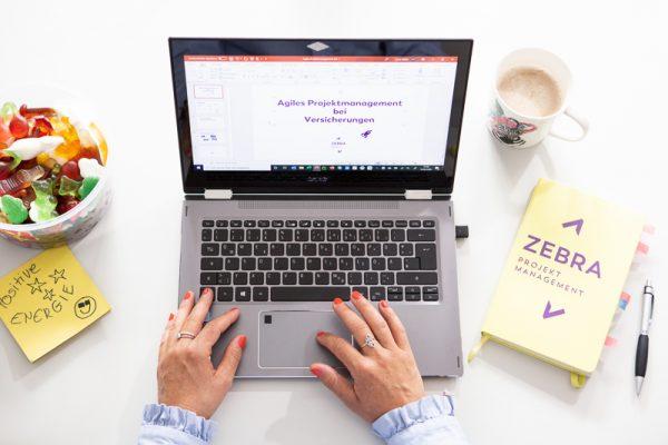 Carlas Hände sind von oben zu sehen. Sie schreibt etwas am Laptop.