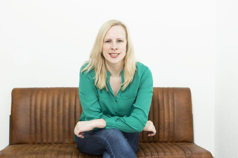 Ein Frau sitzt auf einer braunen Lederbank und lehnt sich auf ihre Knie.
