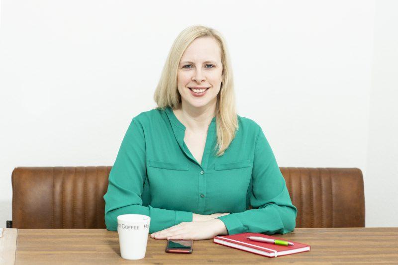 Ein Frau sitzt an einem Tisch und hat ein Notizbuch und einen Kaffeebecher vor sich