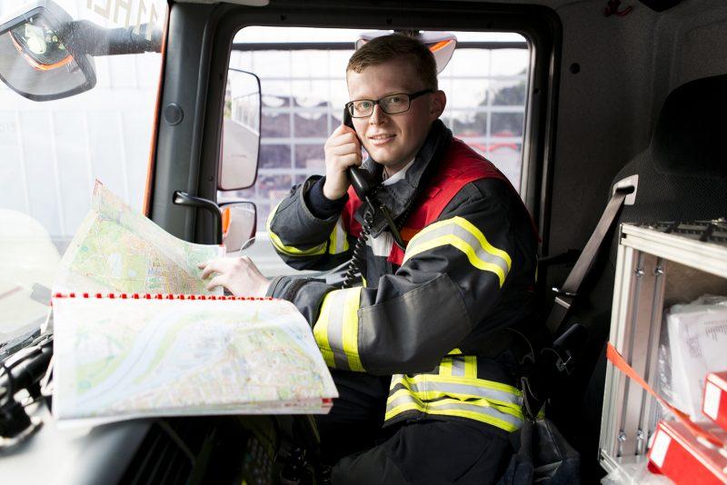 Der Feuerwehrmann sitzt über einer Karte und hat den Telefonhörer am Ohr