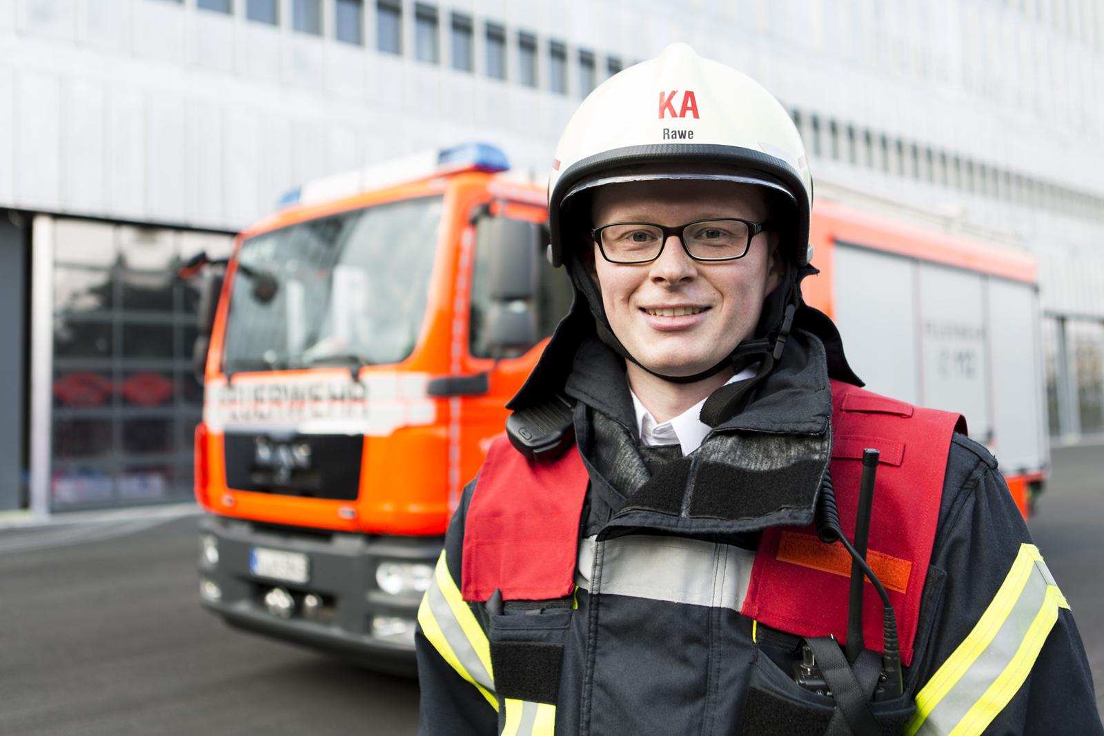 Ein Feuerwehrmann steht vor seinem Feuerwehrauto