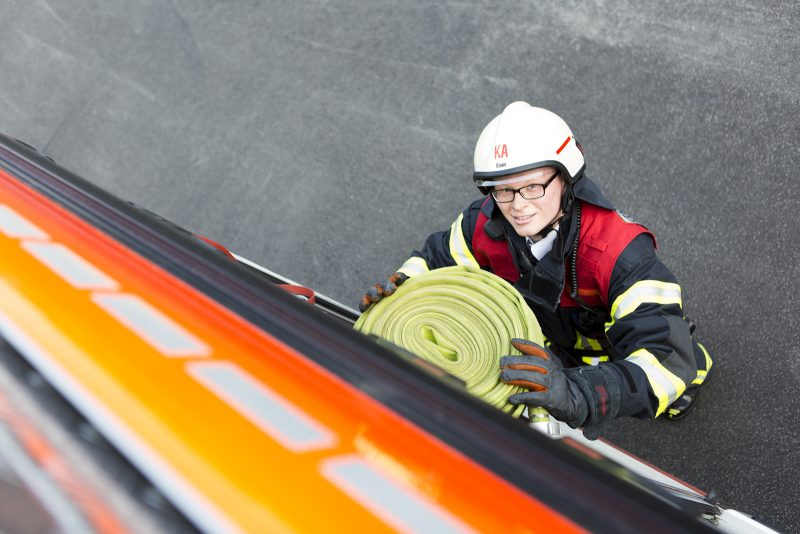 Ein Feuerwehrmann holt einen Wasserschlauch aus dem Feuerwehrauto
