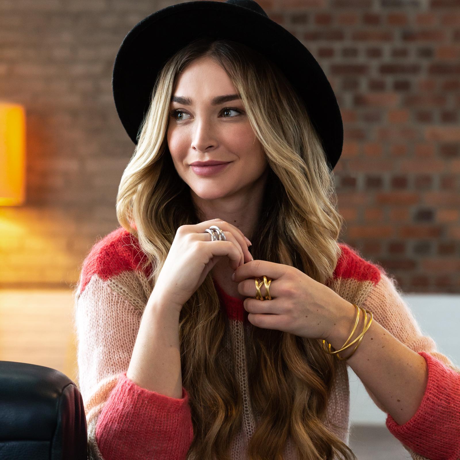 Eine Frau sitzt auf einem Sessel und schaut zur Seite. Sie trägt einen Hut und hält ihre Hände vor dem Körper. An beiden Händen trägt sie Schmuck.
