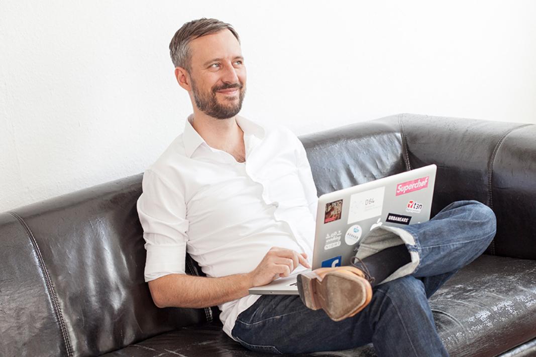 Ein Mann sitzt mit einem Laptop auf dem Sofa und lacht zur Seite