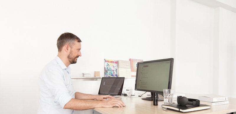 EIn Mann sitzt an seinem Schreibtisch und arbeitet am Computer