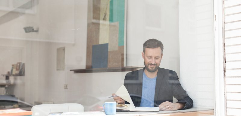 Ein Mann sitzt hinter einem Fenster und blättert durch ein Notizbuch