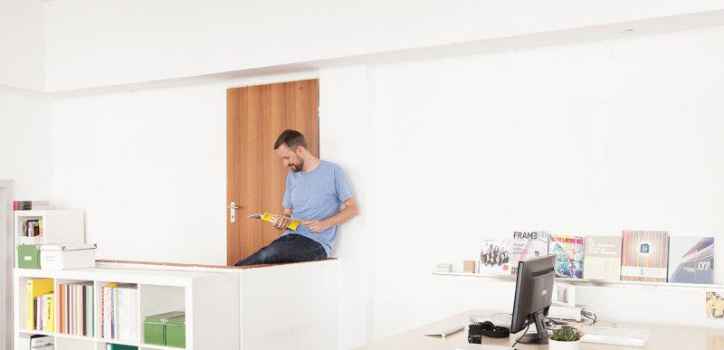 Ein Mann sitzt auf einer Mauer und blättert durch ein Magazin