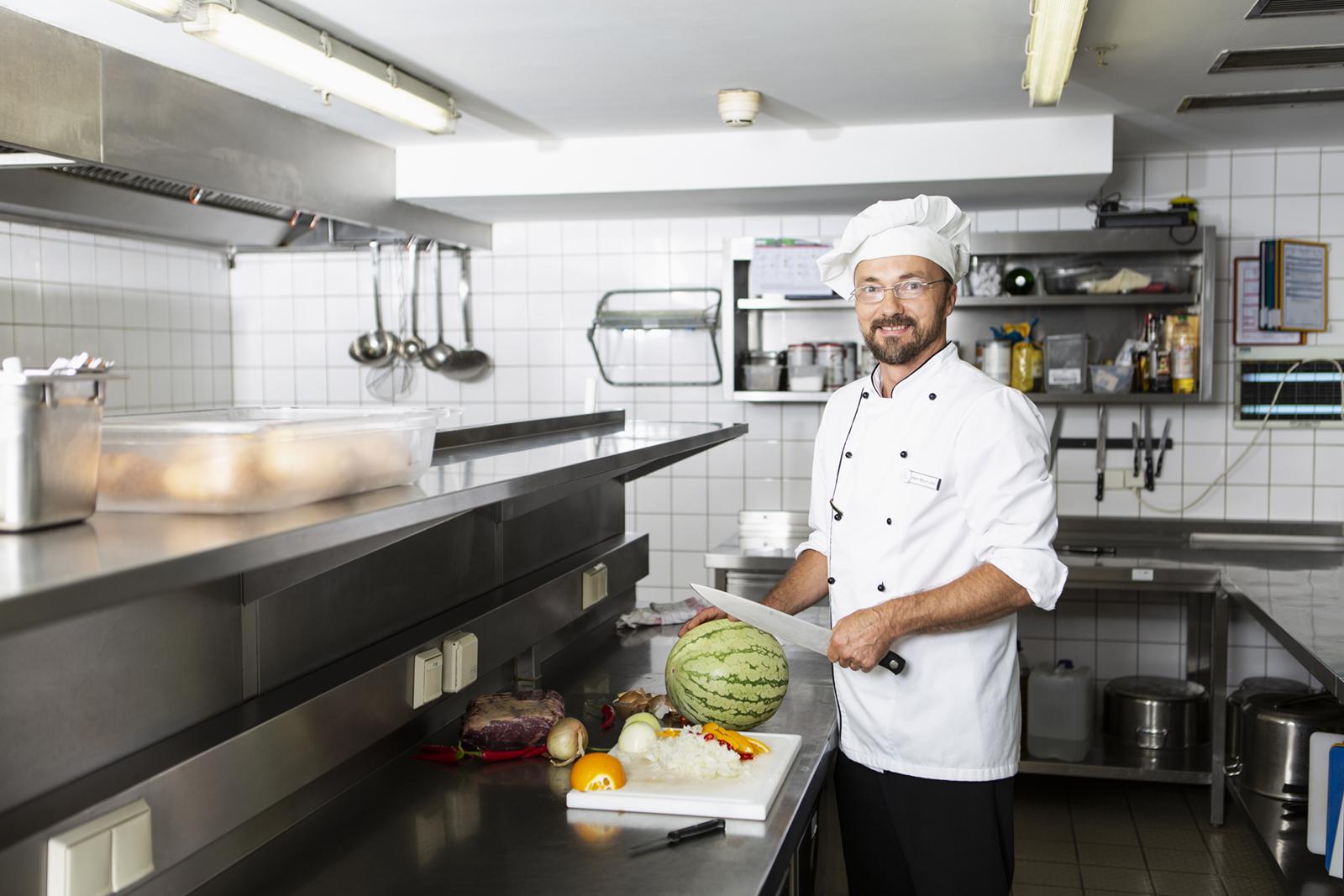 Ein Koch steht in der Küche und schneidet eine Melone auf