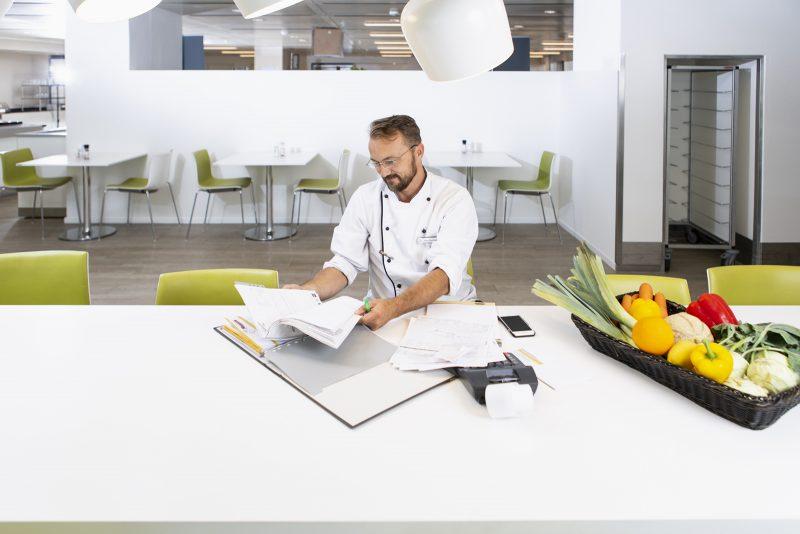 Ein Koch sitzt in an einem großen Tisch in der Kantine und sortiert Belege