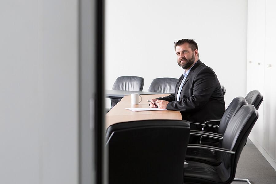 Ein Mitarbeiter sitzt in einem Konferenzraum und schaut in die Kamera