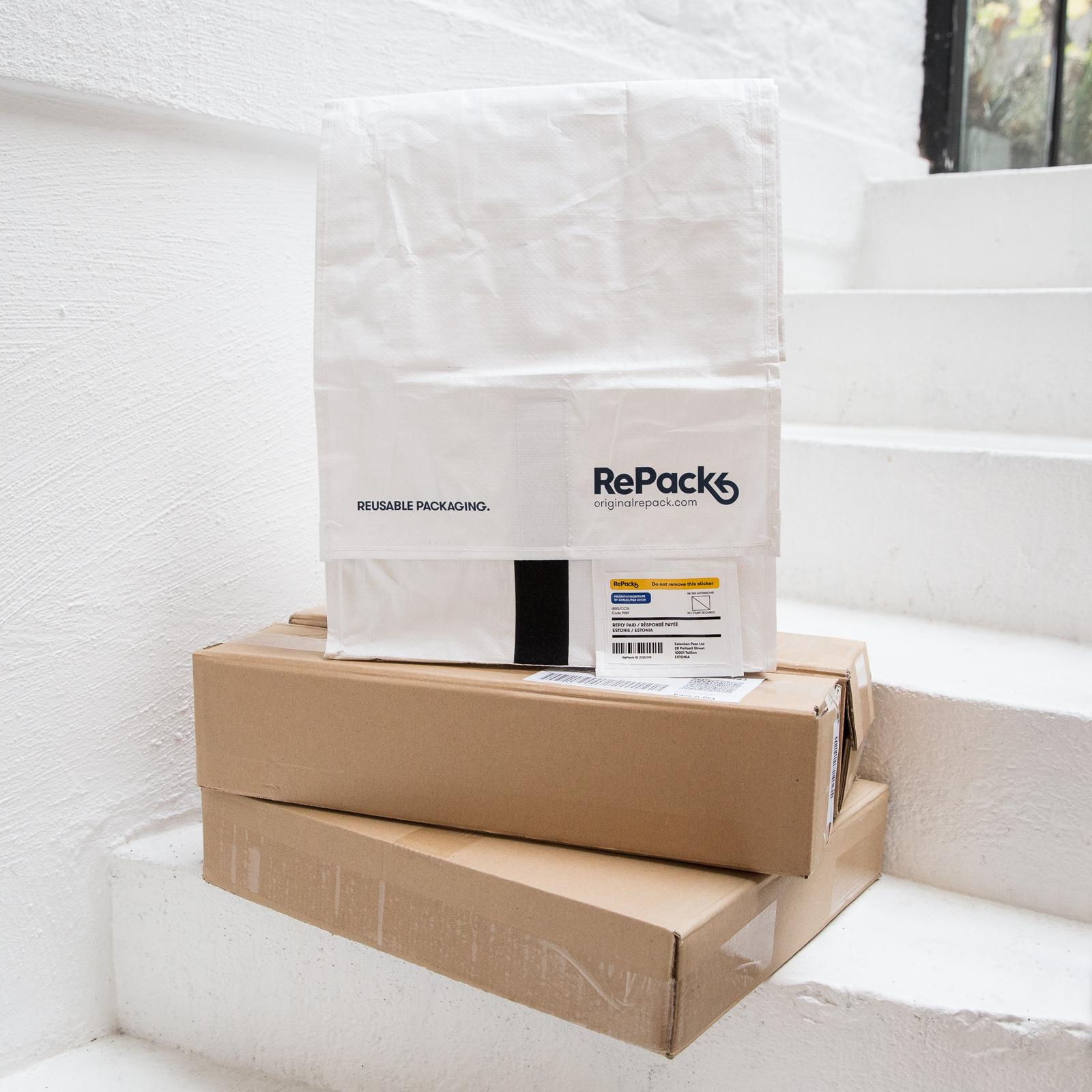 Auf einer Treppe steht eine nachhaltige Versandtasche