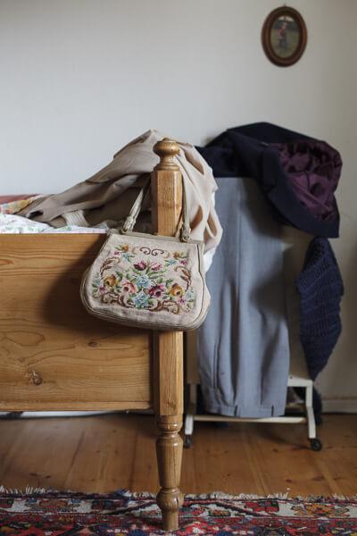 Am Bettpfosten hängt eine bestickte Handtasche