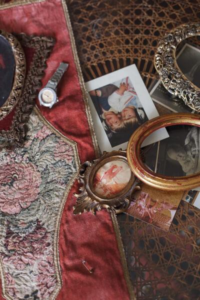 Auf dem Tisch liegen Bilder, Bilderrahmen und eine Armbanduhr