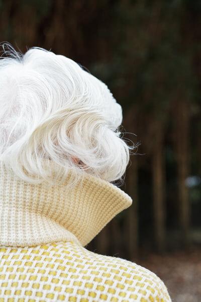 Nanis Kopf ist von hinten zu sehen. Sie trägt eine dicke Wolljacke und ihr Blick geht in Richtung Bäume