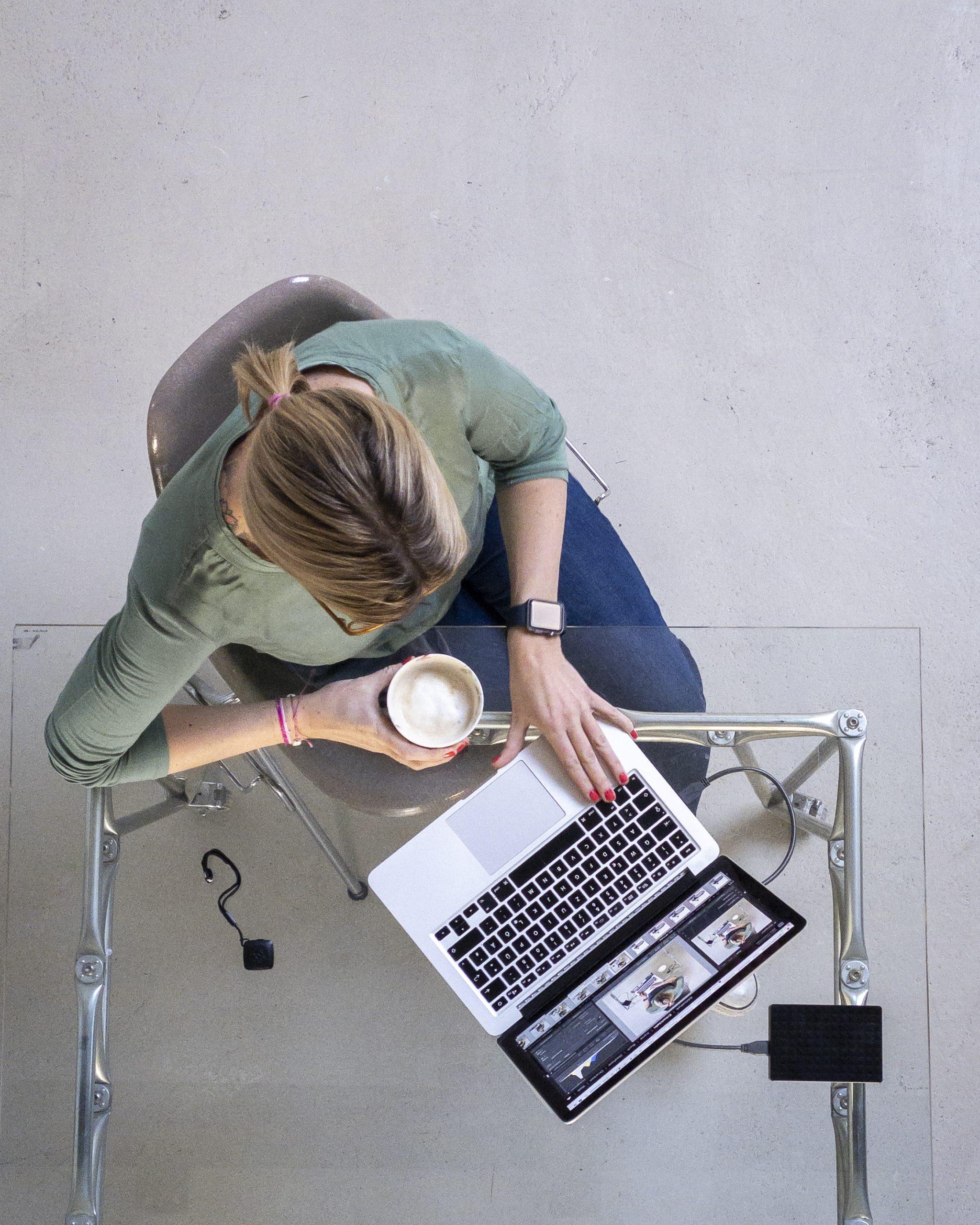 Ein Bild von oben, wie Maxi an ihrem Laptop arbeitet.