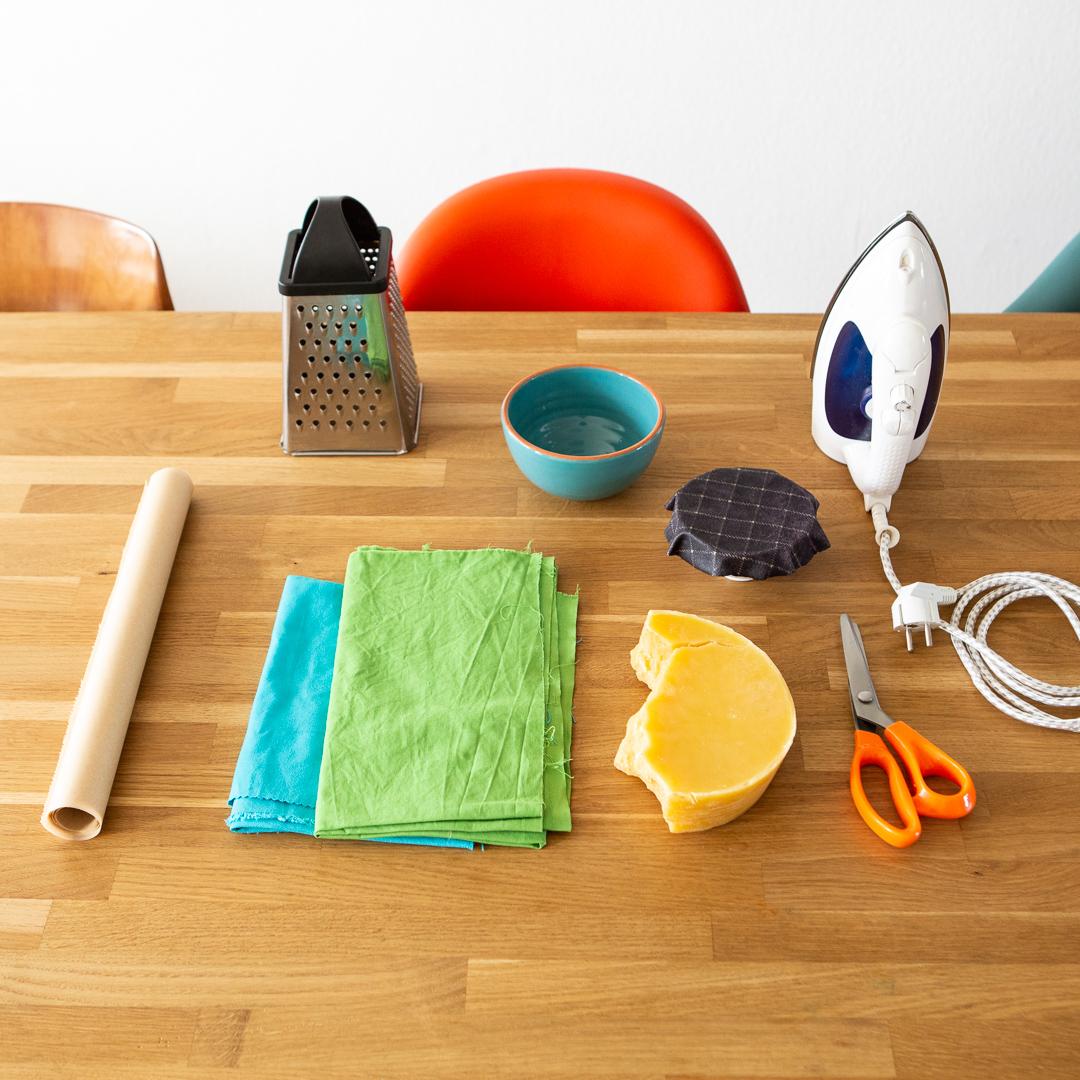 Alles was du brauchst um ein Wachstuch selber zu machen: Bienenwachs, Stoffreste, Backpapier, Bügeleisen, Reibe, Schere
