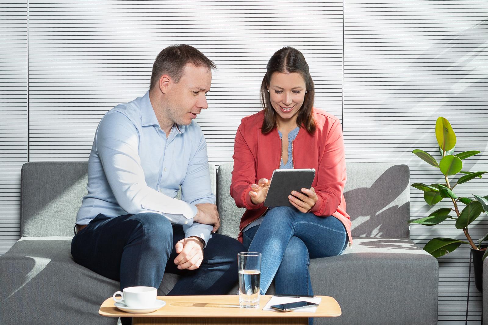 Die beiden Gründer sitzen auf einem Sofa und schauen sich zusammen Inhalte auf dem Tablet an.