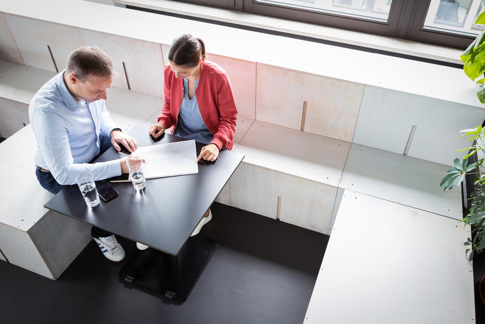 Die beiden Gründer sitzen zusammen an einem Tusch und schauen sich Unterlagen an. Das Foto zeigt die Vogelperspektive.