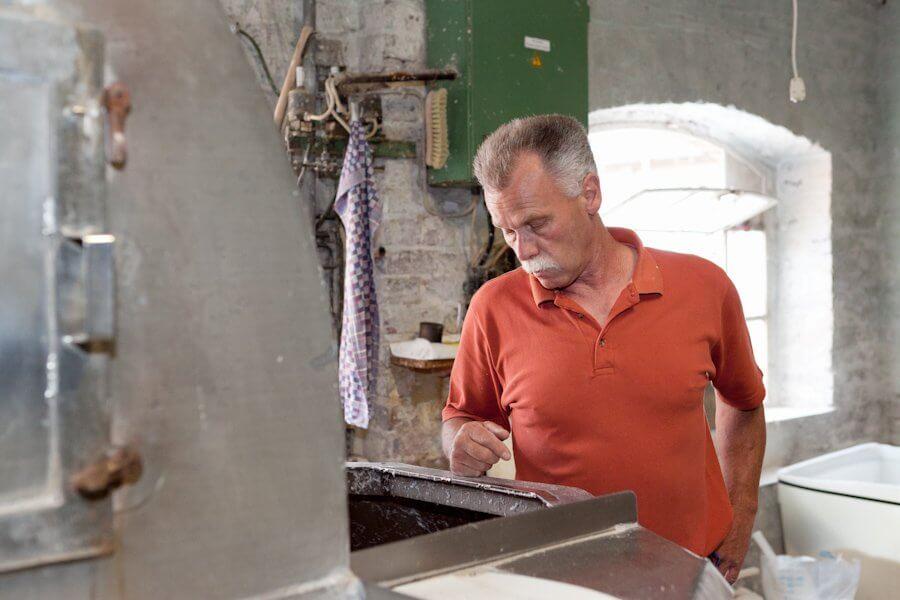 Ein Mann wirft einen Blick in eine Maschine und überprüft die Rohstoff-Wasser Masse