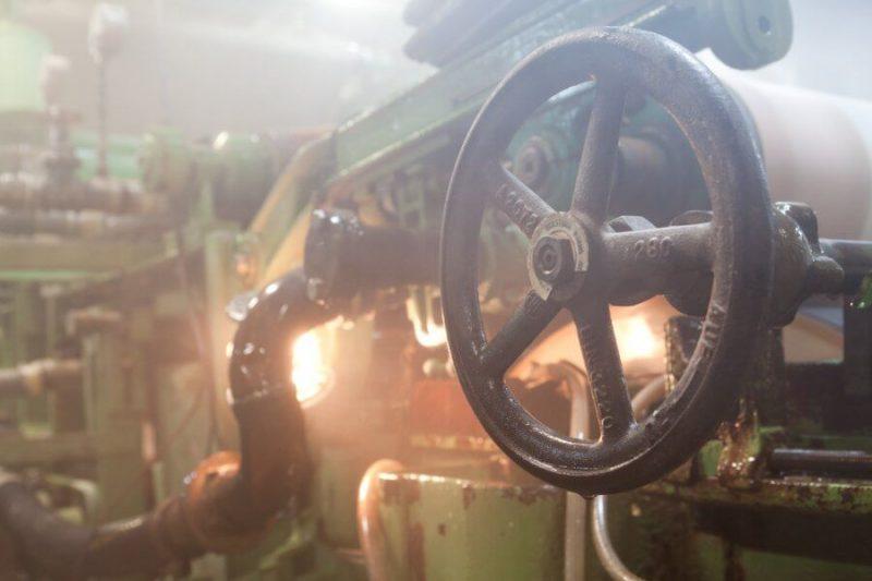 Man sieht einen Teil der Papiermaschine, im Vordergrund ist in großes Rad und von hinten scheint ein Licht.
