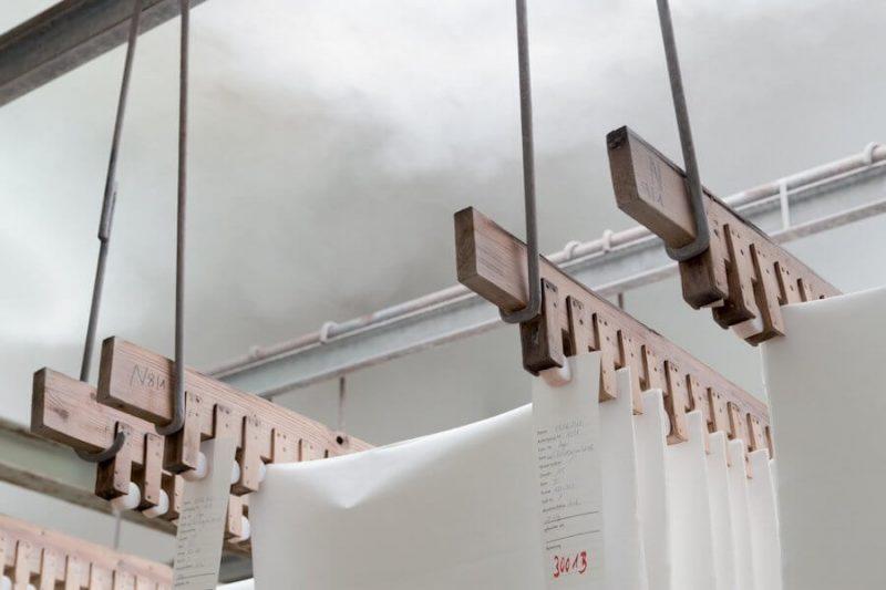 Das Büttenpapier hängt an einer Holzvorrichtung im Feuchtraum
