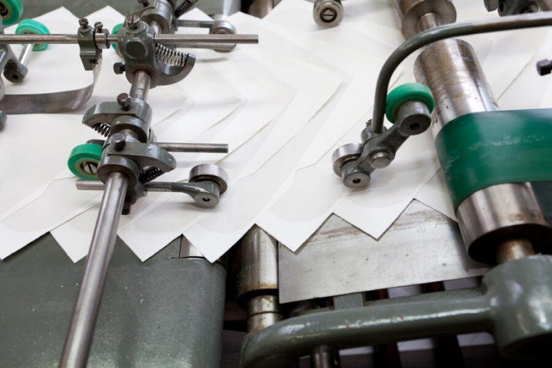 Die Briefumschläge laufen über eine Maschine in der sie gummiert werden