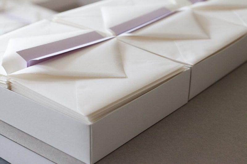 Fertige Briefumschläge liegen in einm Karton