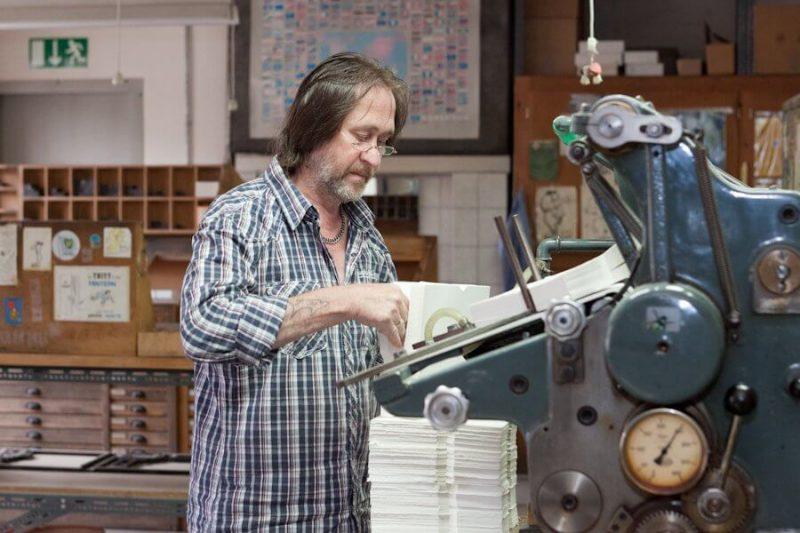 Der Drucker steht an der Maschine und legt Briefumschläge zum Druck ein