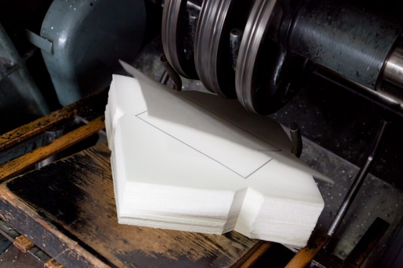 Die Kuverts laufen aus der Druckmaschine. Sie haben einen Trauerrand bekommen.