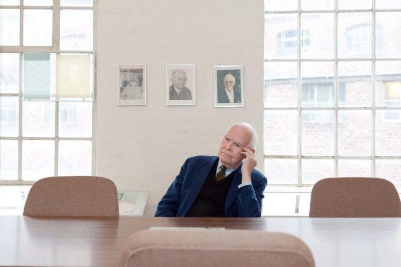 Der Seniorchef sitzt an einem Tisch und schaut nachdenklich zur Seite.