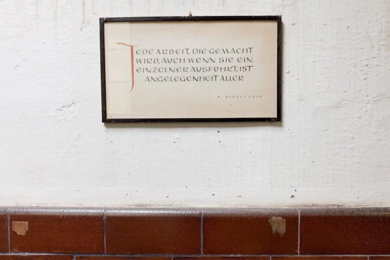 Ein Bild hängt an der Wand mit dem Text: Jede Arbeit, die gemacht wird, auch wenn sie ein Einzelner ausgeführt hat, ist Angelegenheit aller.